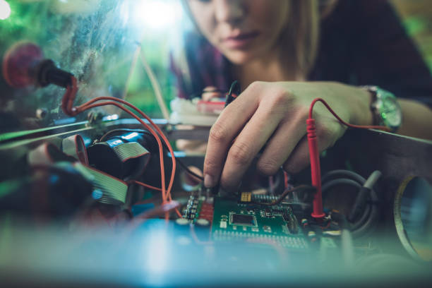 close up of a woman repairing electrical component of a computer. - electronics industry stock pictures, royalty-free photos & images