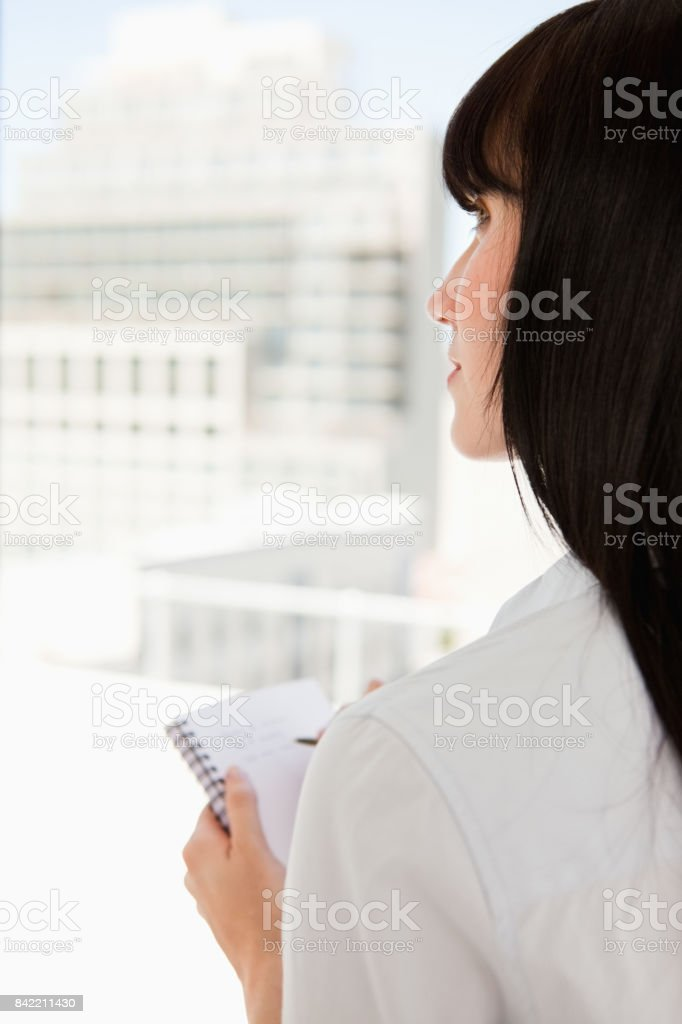 Close up of a woman staring upwards with a notpad in her hand stock photo