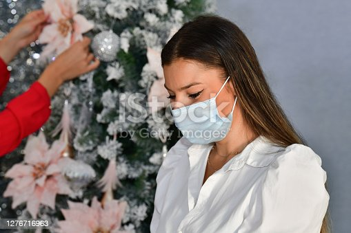 Close up of a woman using a surgical mask with an out of focus Christmas tree being decorated at the back. Christmas holiday and safety concept.