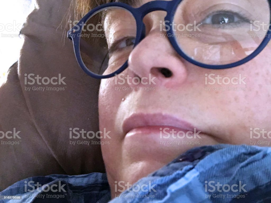 Close up of a woman with glasses to see up close stock photo