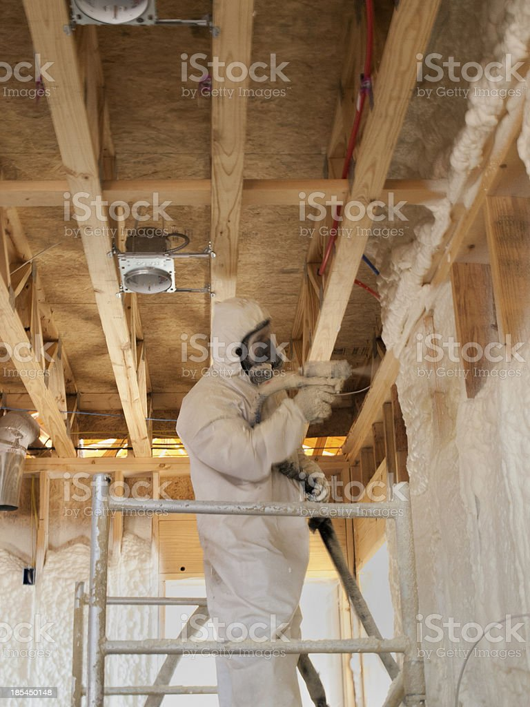 Close up of a worker blowing insulation stock photo