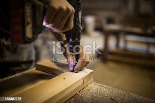 Close up of unrecognizable carpenter using drill while working on furniture in a workshop.