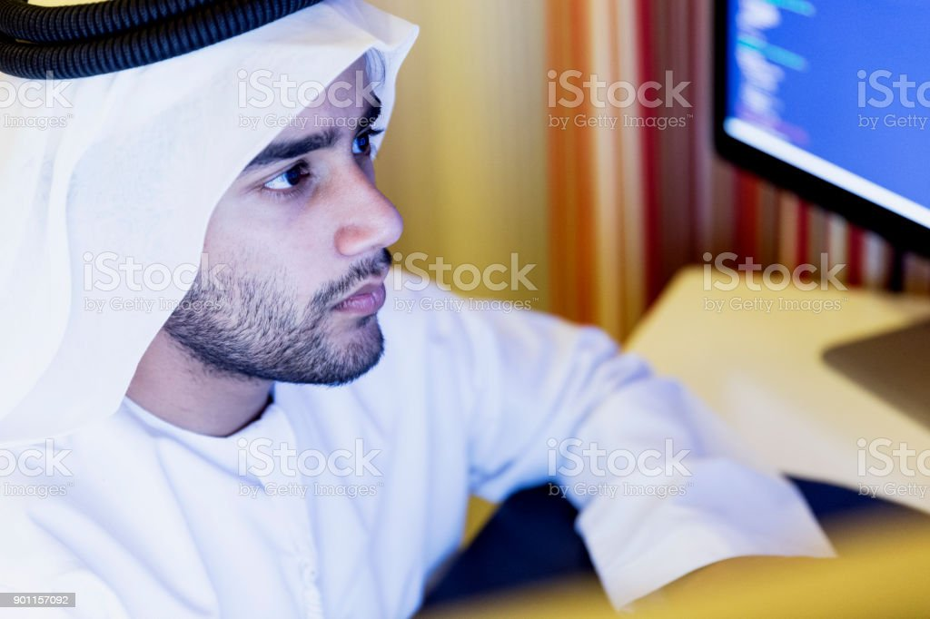 Young Arab working from his home office at night to complete his...