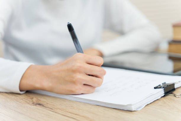 Close up of a young cheerful Asian student female university student studying in self study room in the university library to do her assignment and prepare for examination. stock photo