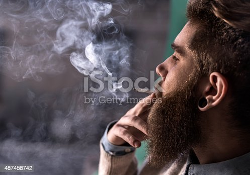 istock Close up of a young hipster smoking cigarette. 487458742