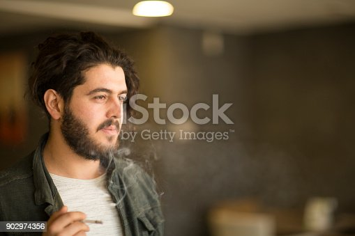 istock Close up of a young hipster smoking cigarette. 902974356