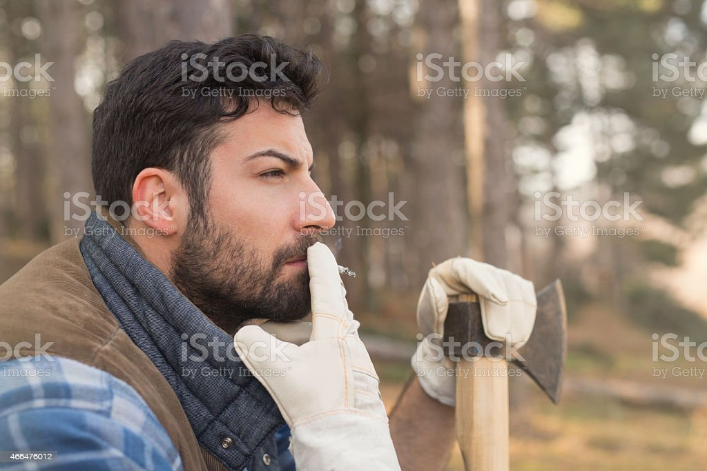 Close up of a young lumberjack man enjoying cigarettes stock photo