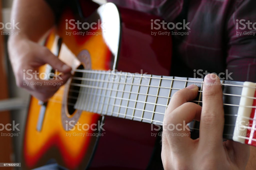 Close up of a young man playing a guitar stock photo