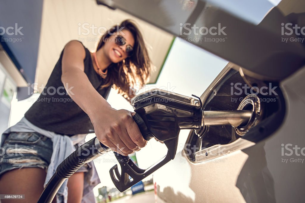 Close up of a young woman at gas station. stock photo