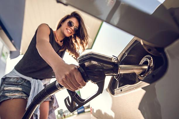 primer plano de una mujer joven en la gasolinera. - echar combustible fotografías e imágenes de stock