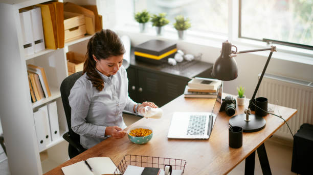 Close up of a young woman having lunch in her office stock photo
