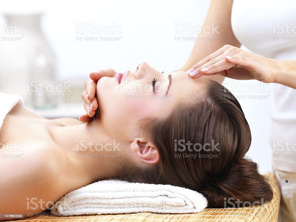 Close up of a young woman receiving facial massage stock photo