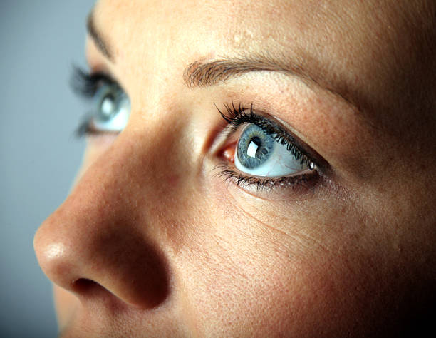 A close up of a young woman's blue eyes stock photo