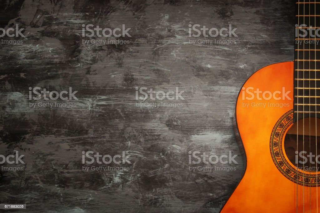 Close up of acoustic guitar against a wooden background stock photo