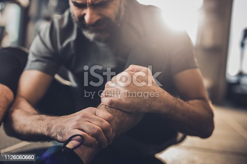 istock Close up of active mature man feeling pain in his leg in a gym. 1126060660