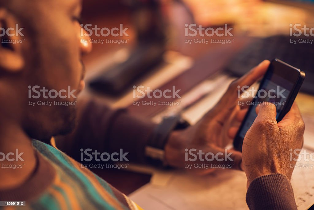 Close up of African American man text messaging on phone. stock photo