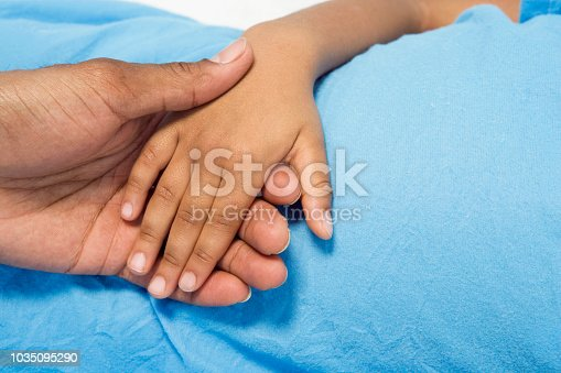 istock Close up of African boy holding parent's hand 1035095290