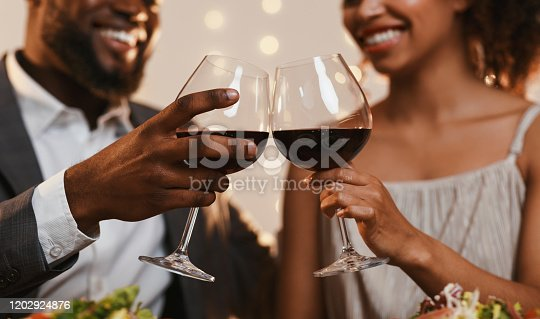 istock Close up of african couple toasting with red wine 1202924876