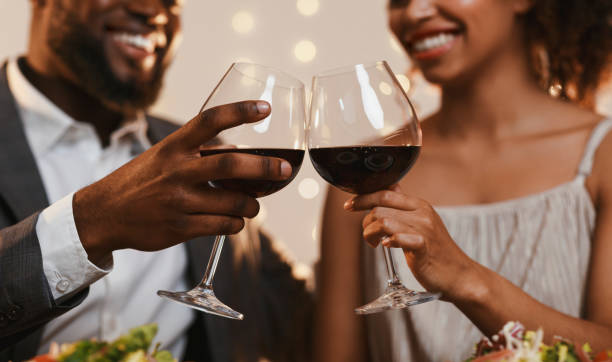 Close up of african couple toasting with red wine Close up of cheerful african american couple toasting with red wine, celebrating anniversary flirting stock pictures, royalty-free photos & images