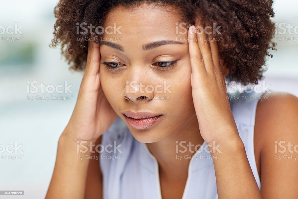 close up of african young woman touching her head stock photo
