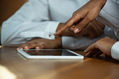 Close up of african-american human's hands using tablet on wooden table. Female hands touching blank screen, shopping online or serfing, browsing internet. Business, sales, online, finance concept.