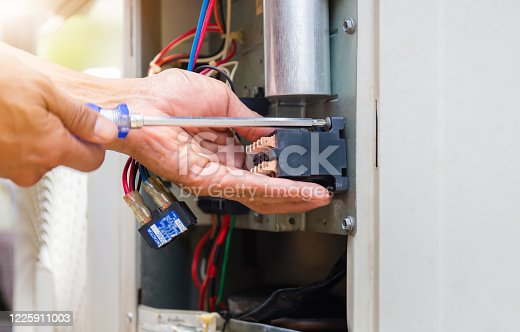 Close up of Air Conditioning Repair, repairman installing magnetic contactor and fixing air conditioning system