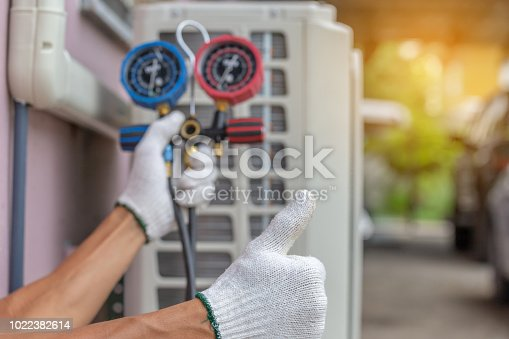 istock Close up of Air Conditioning Repair, repairman on the floor fixing air conditioning system 1022382614