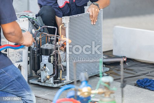 Close up of Air Conditioning Repair team use fuel gases and oxygen to weld or cut metals, Oxy-fuel welding and oxy-fuel cutting processes, repairman on the floor fixing air conditioning system