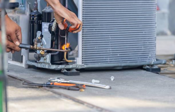 zbliżenie klimatyzacji zespół naprawczy wykorzystuje gazy paliwowe i tlen do spawania lub cięcia metali, spawanie paliwowo-tlenowe i procesy cięcia tlenowo-paliwowego, naprawa systemu klimatyzacji mocującej podłogę - naprawiać zdjęcia i obrazy z banku zdjęć