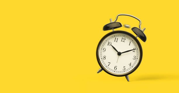 Close up of alarm clock isolated on yellow background stock photo