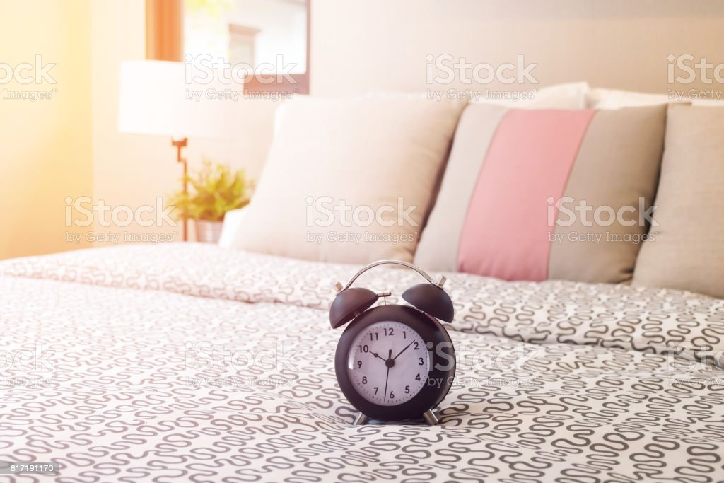 Close Up Of Alarm Clock On Bed With Sunlight In Bedroom Royalty Free Stock  Photo