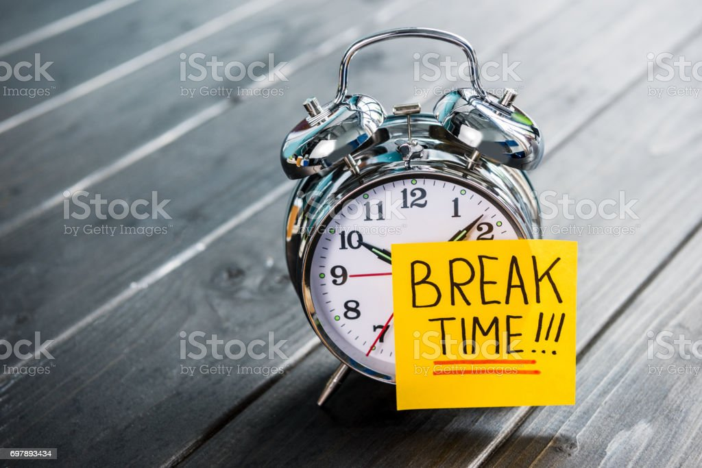 close up of alarm clock with message break time on wooden tabletop stock photo