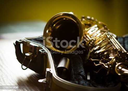 close up of alto saxophone in open case on table against widow light, copy space