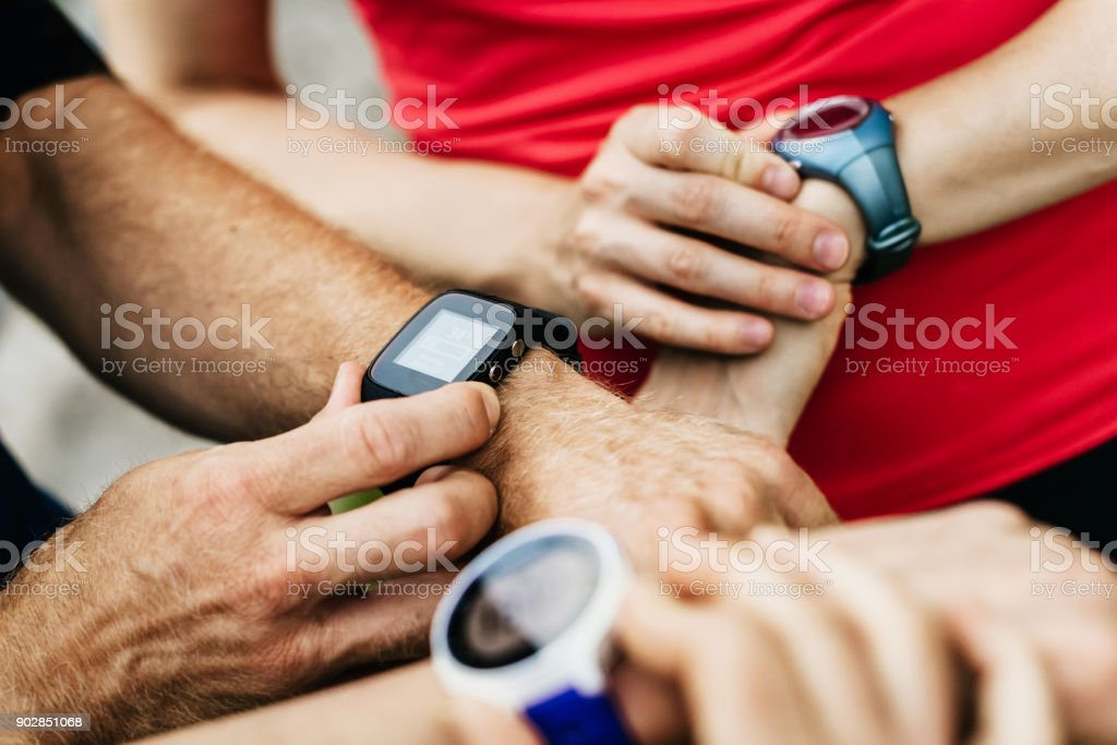 Close Up Of Amateur Athletes Synchronising Smart Watches Together stock photo