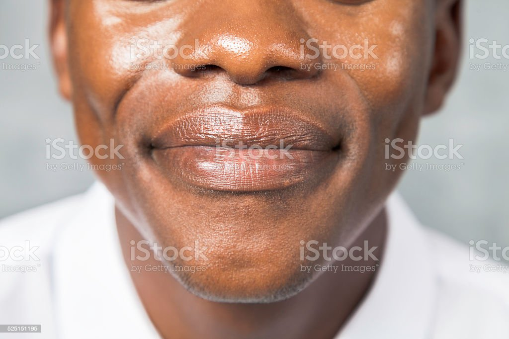 Close up of an african males mouth, smiling. stock photo