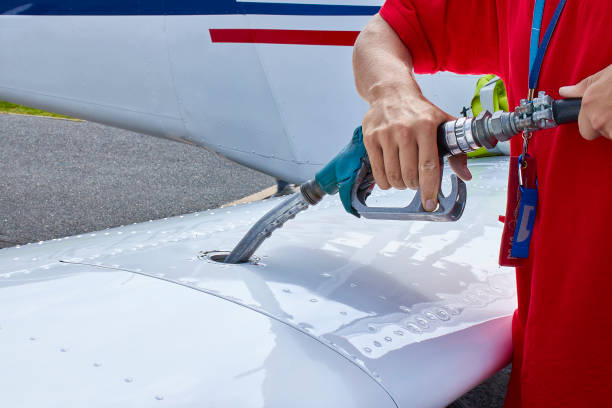 Close up of an aircraft worker fueling low-wing propeller driven airplane stock photo