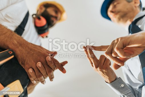 istock Close up of an architect explaining his worker things to do. 1054950096