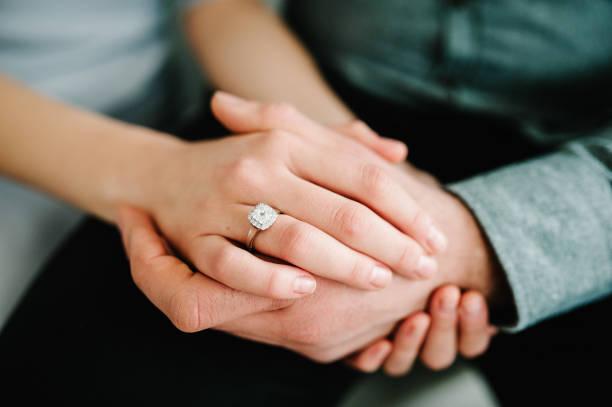 feche acima de um anel de diamante elegante do acoplamento no dedo da mulher. conceito do amor e do casamento. - casamento - fotografias e filmes do acervo