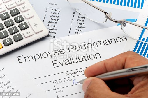 Close up of an Employee Performance Evaluation Form with writing hand