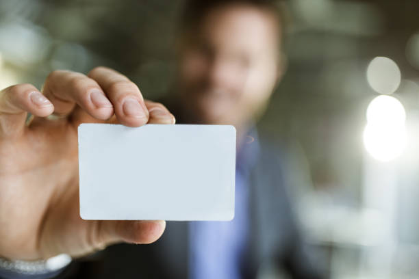 Close up of an empty business card in man's hand. stock photo