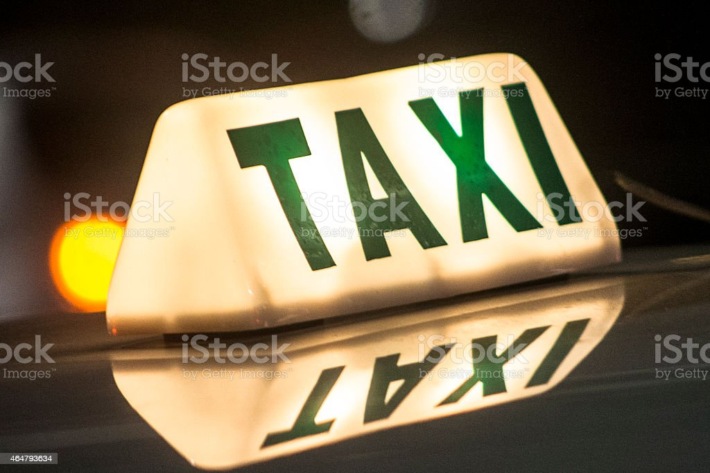 Close up of an illuminated taxi sign and its reflection stock photo