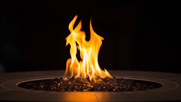 nahaufnahme von einer feuerstelle mit einem großen gelben flamme und schwarzem hintergrund - gaskamin stock-fotos und bilder