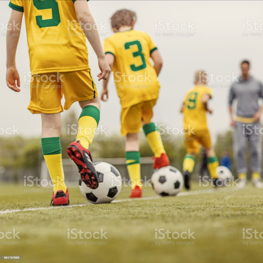 A close up of an unidentified boys soccer team during an intense football training session with a male coach royalty-free stock photo