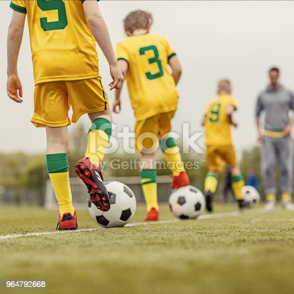 istock A close up of an unidentified boys soccer team during an intense football training session with a male coach 964792668