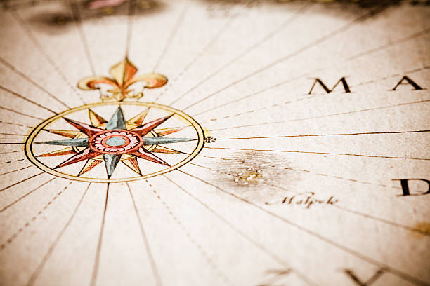 Close up of antique style compass on old map stock photo