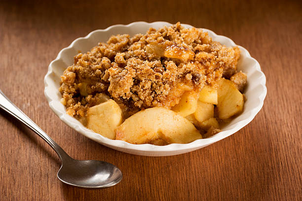 Close up of Apple crisps in a white bowl and a single spoon stock photo