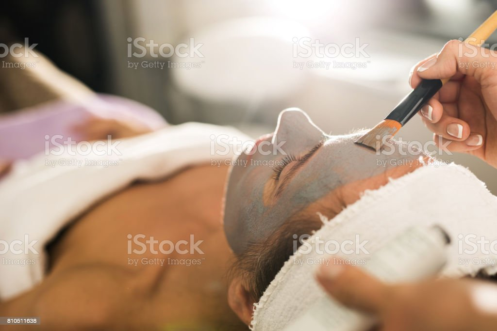 Close up of applying facial mask on woman's face in a beauty salon. stock photo