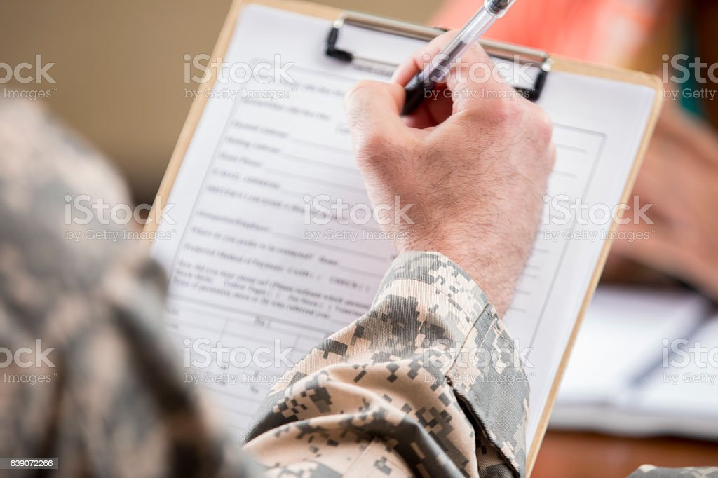 Close up of army veteran completing paperwork for counseling session stock photo