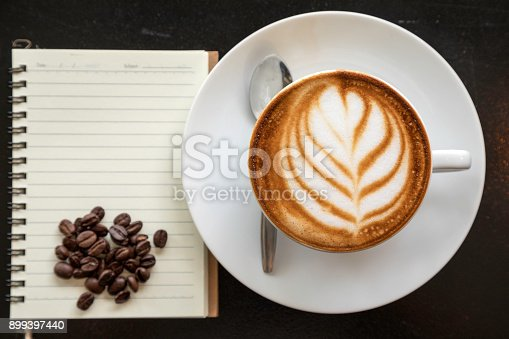 istock Close up of art coffee latte placing with notebook and coffee bean by flat lay 899397440