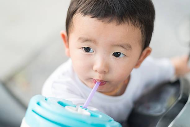 Close up of Asian baby boy drinking water with straw. stok fotoğrafı